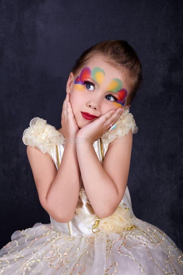 Retrato da menina bonita nos bordos vermelhos do vestido branco com a cara pintada no fundo escuro imagem de stock royalty free