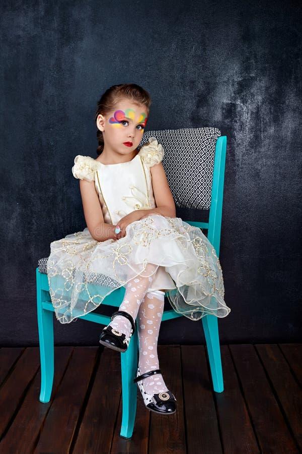 Retrato da menina bonita nos bordos vermelhos do vestido branco com a cara pintada que senta-se em uma cadeira no fundo escuro fotos de stock royalty free