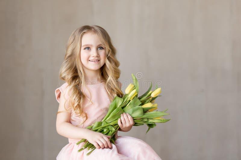Retrato da menina bonita nova muito bonita com as tulipas amarelas das flores, sorrindo Foto interna Tema da mola Close-up Copie  foto de stock