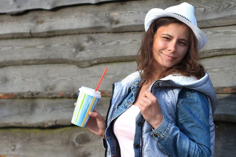Retrato da menina bonita nova no chapéu de vaqueiro com milk shake à disposição Mulher atrativa no revestimento das calças de bri imagem de stock royalty free