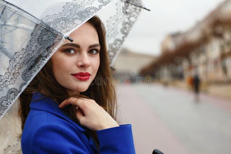 Retrato da menina bonita nova que esconde sob um guarda-chuva foto de stock royalty free