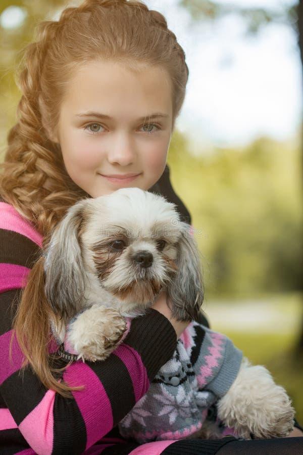 Retrato da menina bonita que abraça seu cão fotografia de stock royalty free