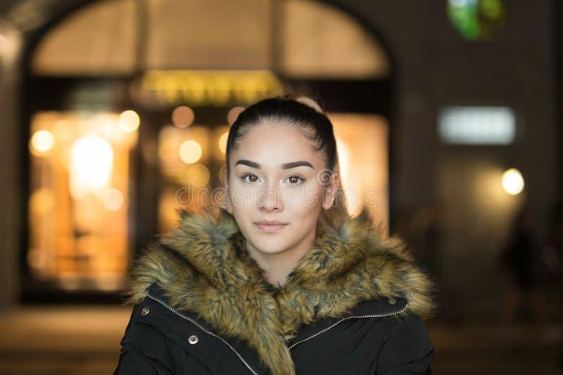 Retrato da menina bonita da raça misturada com o tiro do casaco de pele na luminosidade reduzida na noite foto de stock