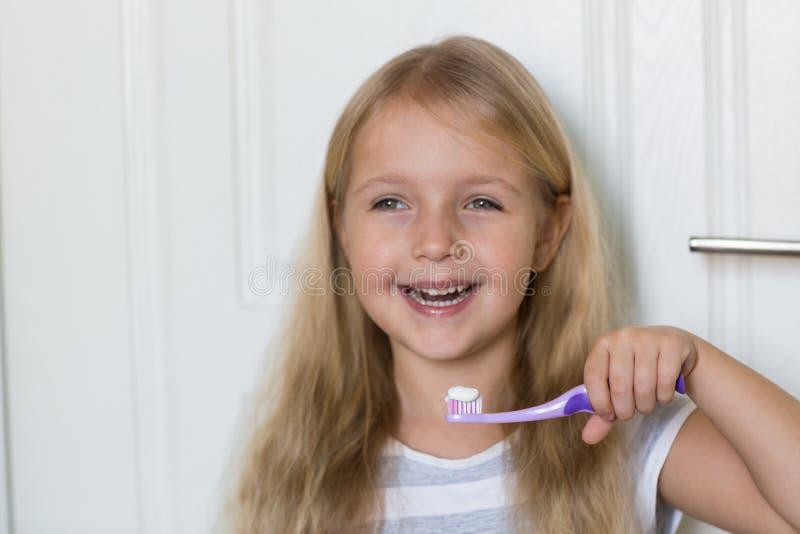 Retrato da menina bonito com cabelo louro que dente de limpeza com escova e dent?frico no banheiro fotos de stock