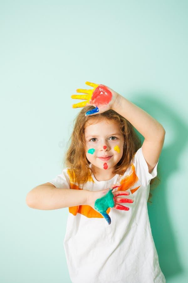 Retrato da menina bonito com cara e mãos pintadas imagem de stock
