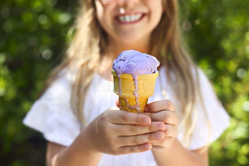 Retrato da menina bonito com a expressão engraçada que mantém o cone de gelado fora contra o fundo brilhante da natureza fotografia de stock