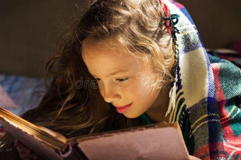 retrato da menina bonito da escola que lê um livro velho no dia frio fotos de stock royalty free