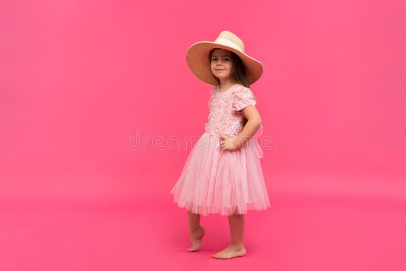 Retrato da menina bonito no chapéu de palha e no vestido cor-de-rosa no estúdio no fundo cor-de-rosa Copie o espaço para o texto imagens de stock