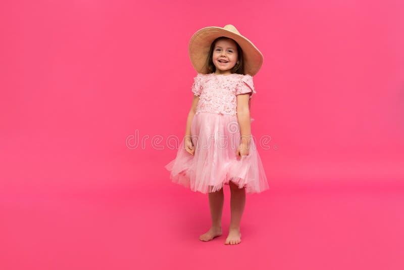 Retrato da menina bonito no chapéu de palha e no vestido cor-de-rosa no estúdio no fundo cor-de-rosa Copie o espaço para o texto fotografia de stock