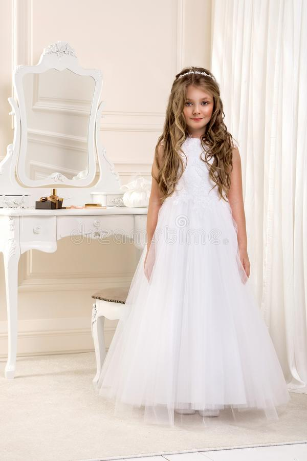 Retrato da menina bonito no vestido e na grinalda brancos na primeira porta da igreja do fundo do comunhão santamente fotografia de stock royalty free