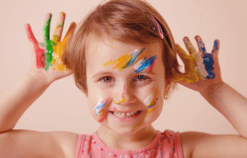 Retrato da menina bonito pequena com a composição colorida das crianças que mostra as mãos pintadas Conceito da felicidade fotografia de stock