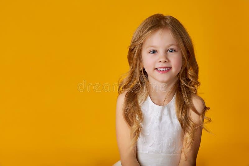 Retrato da menina bonito pequena de sorriso alegre no fundo amarelo isolado imagens de stock royalty free
