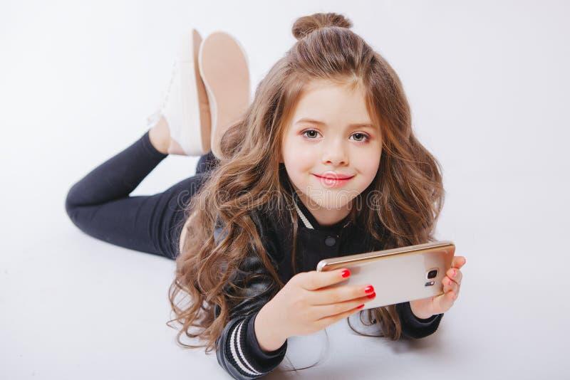 Retrato da menina bonito que coloca no assoalho com telefone Jogando jogos imagem de stock