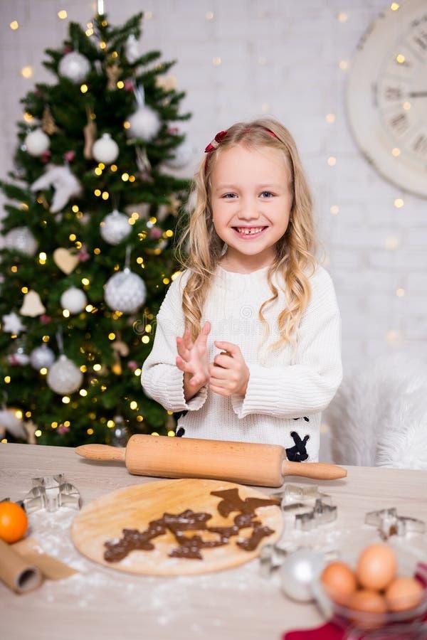 Retrato da menina bonito que faz cookies do Natal na cozinha com C foto de stock royalty free