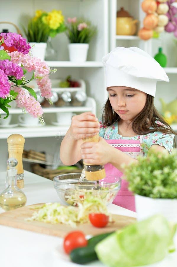 Retrato da menina bonito que prepara a salada fresca deliciosa imagem de stock