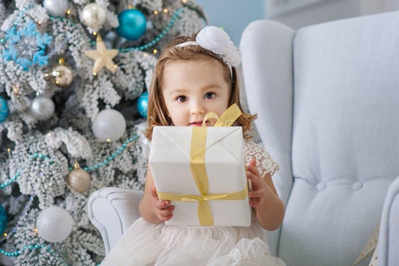 Retrato da menina bonito que sorri e que guarda caixas com os presentes perto da árvore de Natal Ano novo Divertimento do feriado fotografia de stock royalty free
