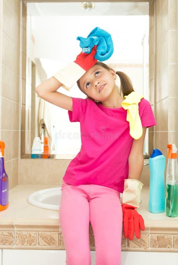 Retrato da menina cansado após ter limpado o banheiro que senta-se no dissipador imagem de stock