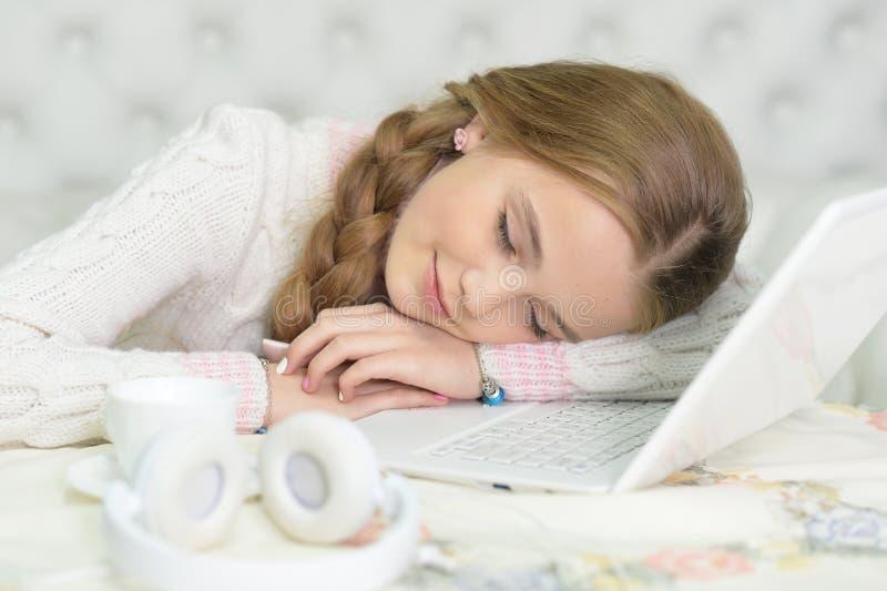 Retrato da menina cansado do preteen que dorme com portátil fotos de stock royalty free