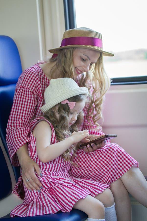 Retrato da menina caucasiano com sua mamã nos chapéus com cabelo ondulado usando um smartphone no trem fotografia de stock