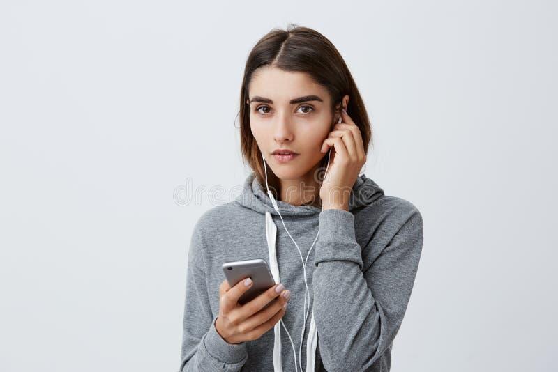 Retrato da menina caucasiano consideravelmente encantador com cabelo longo escuro em fones de ouvido vestindo do hoodie cinzento  imagens de stock