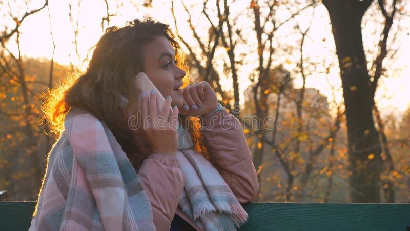 Retrato da menina caucasiano encaracolado-de cabelo concentrada que senta-se no banco e que fala no telefone celular no parque ou fotos de stock royalty free