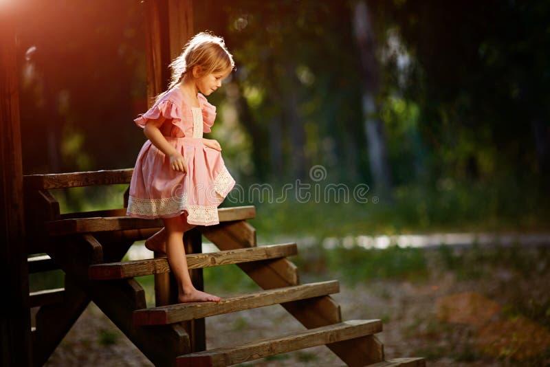Retrato da menina caucasiano pequena que veste o vestido cor-de-rosa que está na ponte de madeira, cobrindo a cara e gritando na  fotografia de stock royalty free