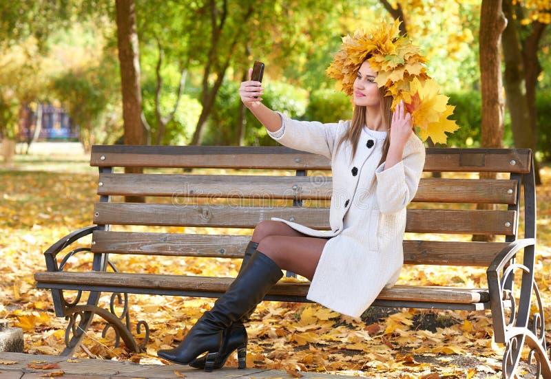 Retrato da menina com as folhas na cabeça que toma o selfie no parque da cidade do outono fotografia de stock royalty free