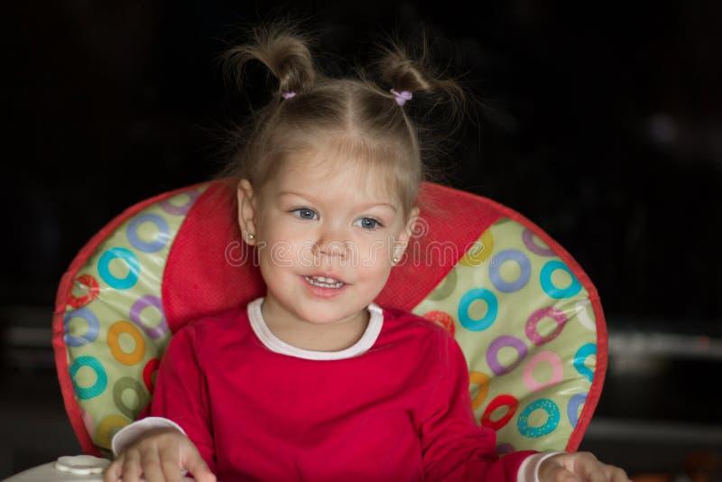 Retrato da menina com assento pensativo do olhar e do sorriso na cadeira fotos de stock royalty free