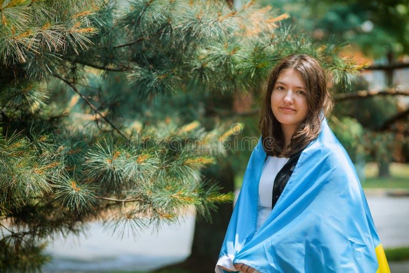 Retrato da menina com nacional uma bandeira ucraniana no parque exterior imagens de stock royalty free