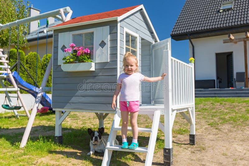 Retrato da menina com o cão na casa bonita do jardim imagem de stock