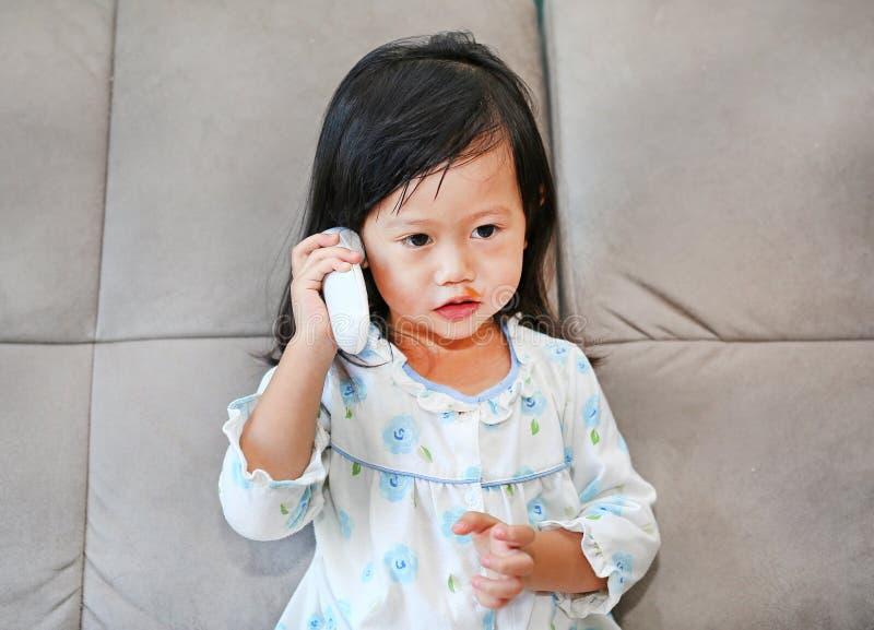 Retrato da menina da criança com uma medição do termômetro de orelha imagem de stock