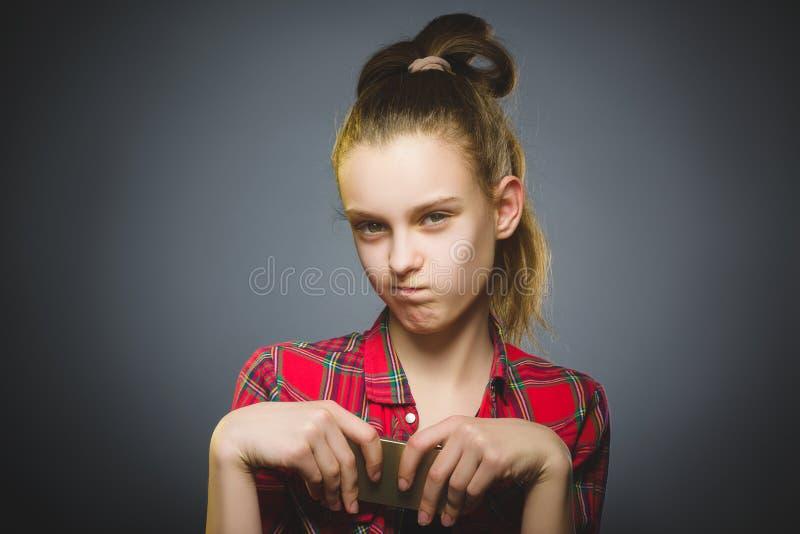 Retrato da menina da ofensa com móbil ou telefone celular Emoção humana negativa foto de stock