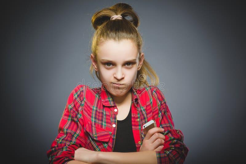 Retrato da menina da ofensa com móbil ou telefone celular Emoção humana negativa imagem de stock royalty free