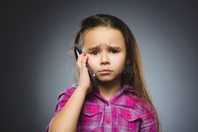 Retrato da menina da ofensa com móbil ou telefone celular Emoção humana negativa fotos de stock