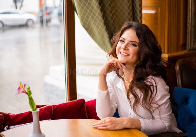 Retrato da menina de encantamento na cafetaria moderna, café da manhã agradável da mulher no café após o trabalho em sua tabuleta fotografia de stock