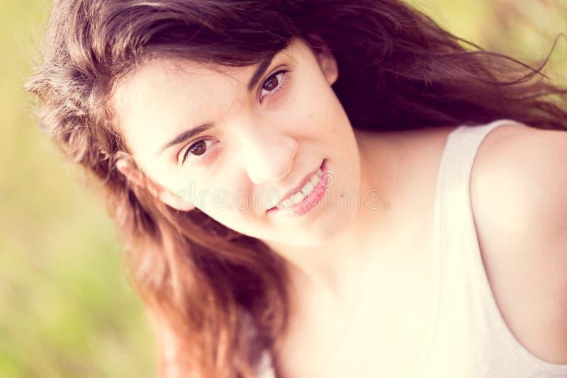 Retrato da menina de sorriso bonita com cabelo preto longo na menina de sorriso do gardenl com cabelo preto longo no prado fotos de stock royalty free
