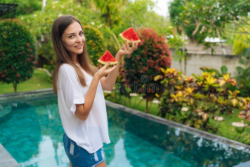 Retrato da menina de sorriso bonita com duas partes de melancia em suas mãos fotos de stock