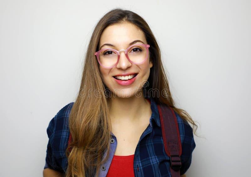 Retrato da menina de sorriso bonita do estudante Estudante novo do lerdo com vidros no fundo branco foto de stock royalty free