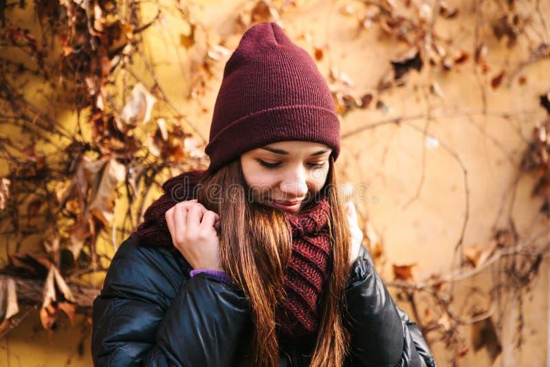 Retrato da menina de sorriso bonita positiva nova que ajusta o lenço no outono Bom humor em algum tempo imagem de stock