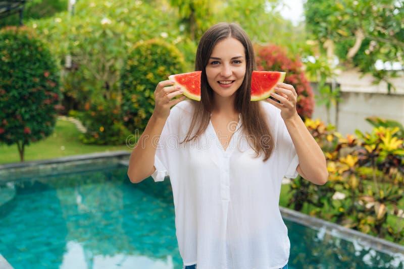 Retrato da menina de sorriso bonita que guarda partes de melancia perto de sua cara imagens de stock royalty free