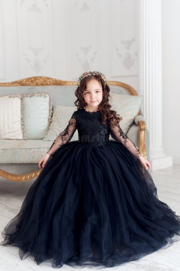 Retrato da menina de sorriso bonito no vestido macio da princesa preta fotografia de stock