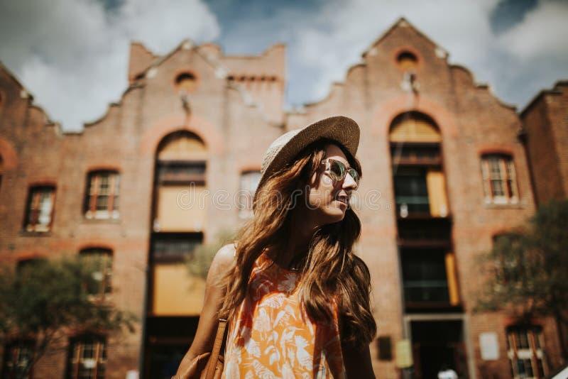 Retrato da menina de sorriso bonito nos óculos de sol com construções da cidade no fundo foto de stock royalty free