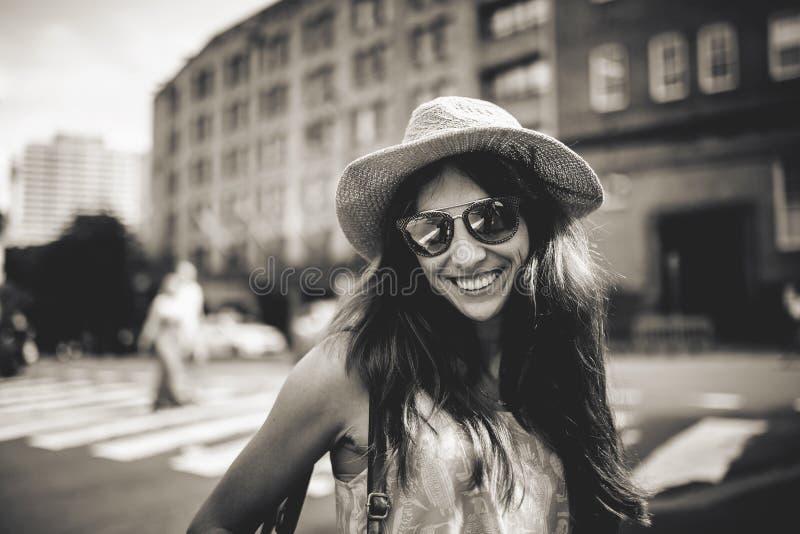 Retrato da menina de sorriso bonito nos óculos de sol com construções da cidade no fundo foto de stock