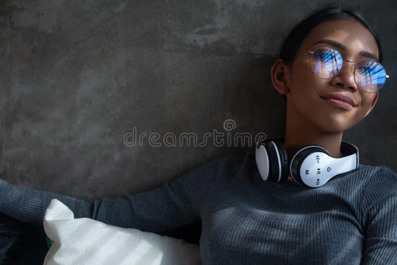 Retrato da menina de sorriso com os fones de ouvido que olham através da janela ao sentar-se no sofá em casa foto de stock