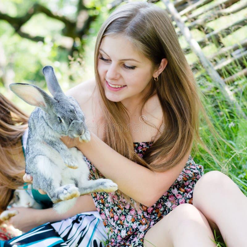 Retrato da menina de sorriso doce da jovem mulher bonita com um coelho no jardim no fundo do verde do verão fora fotos de stock