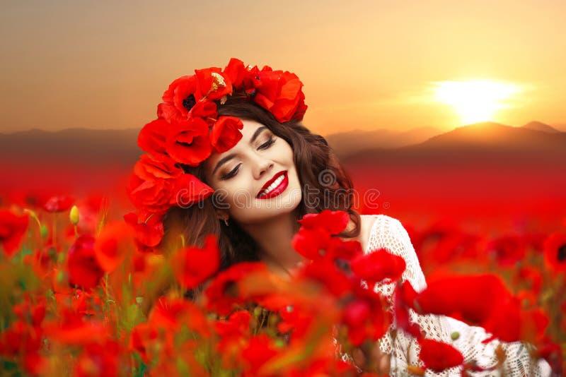 Retrato da menina de sorriso feliz bonita que aprecia na papoila vermelha f fotos de stock royalty free