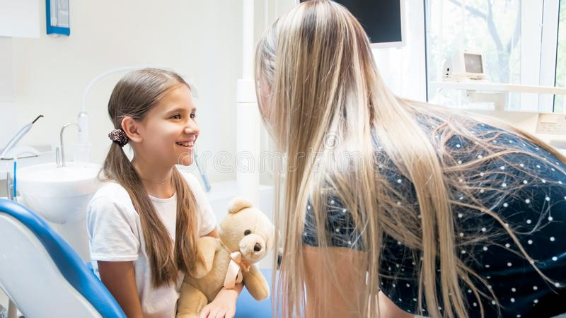 Retrato da menina de sorriso feliz que fala à mãe no escritório do dentista fotografia de stock royalty free