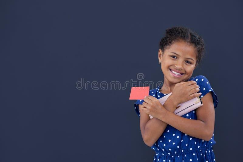 Retrato da menina de sorriso que guarda o cartão de crédito ao guardar a bolsa foto de stock