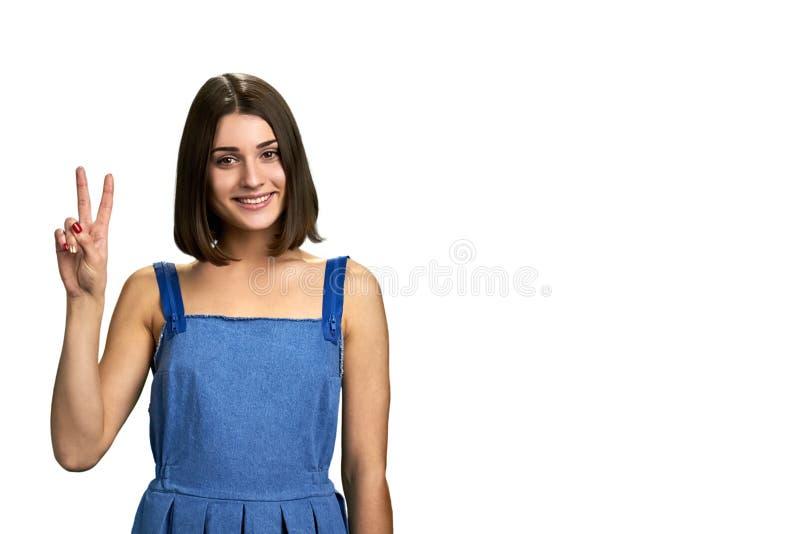 Retrato da menina de sorriso que mostra o gesto da paz fotografia de stock royalty free