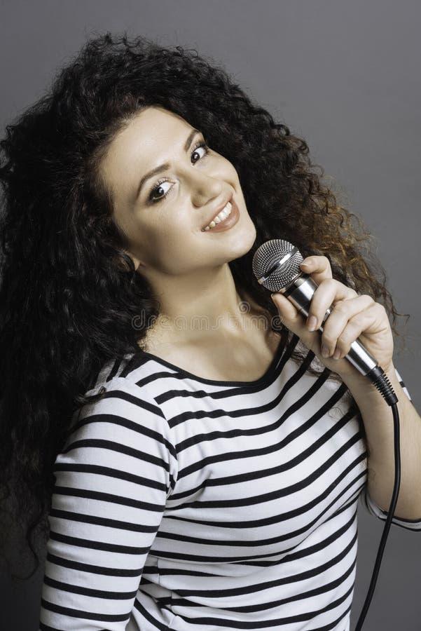 Retrato da menina de vista feliz que guarda o microfone imagens de stock royalty free